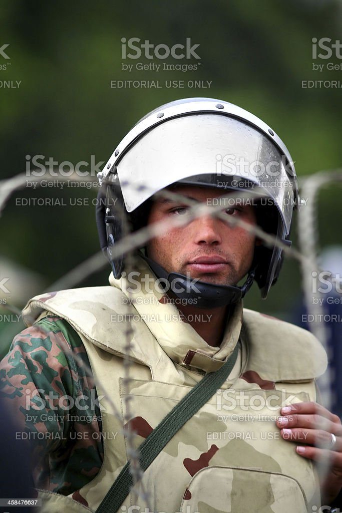 solider guarding barbwired entrance to liberation square stock photo