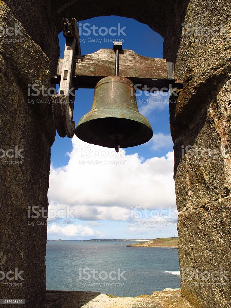 solitary bell in stone arch framing view of sea stock photo