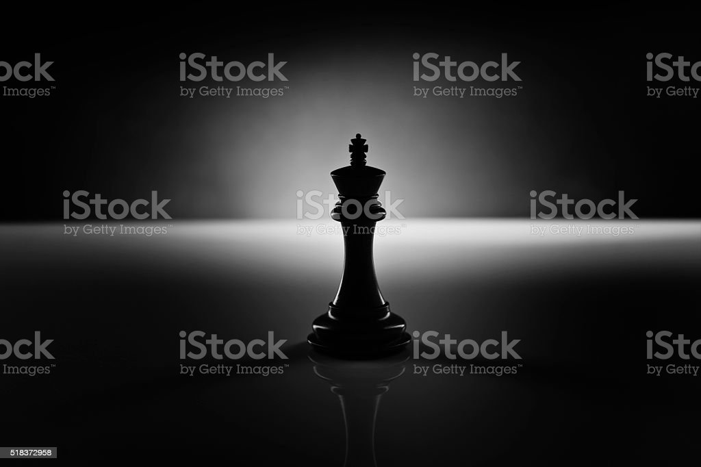 Solitary black chess king in the dark stock photo