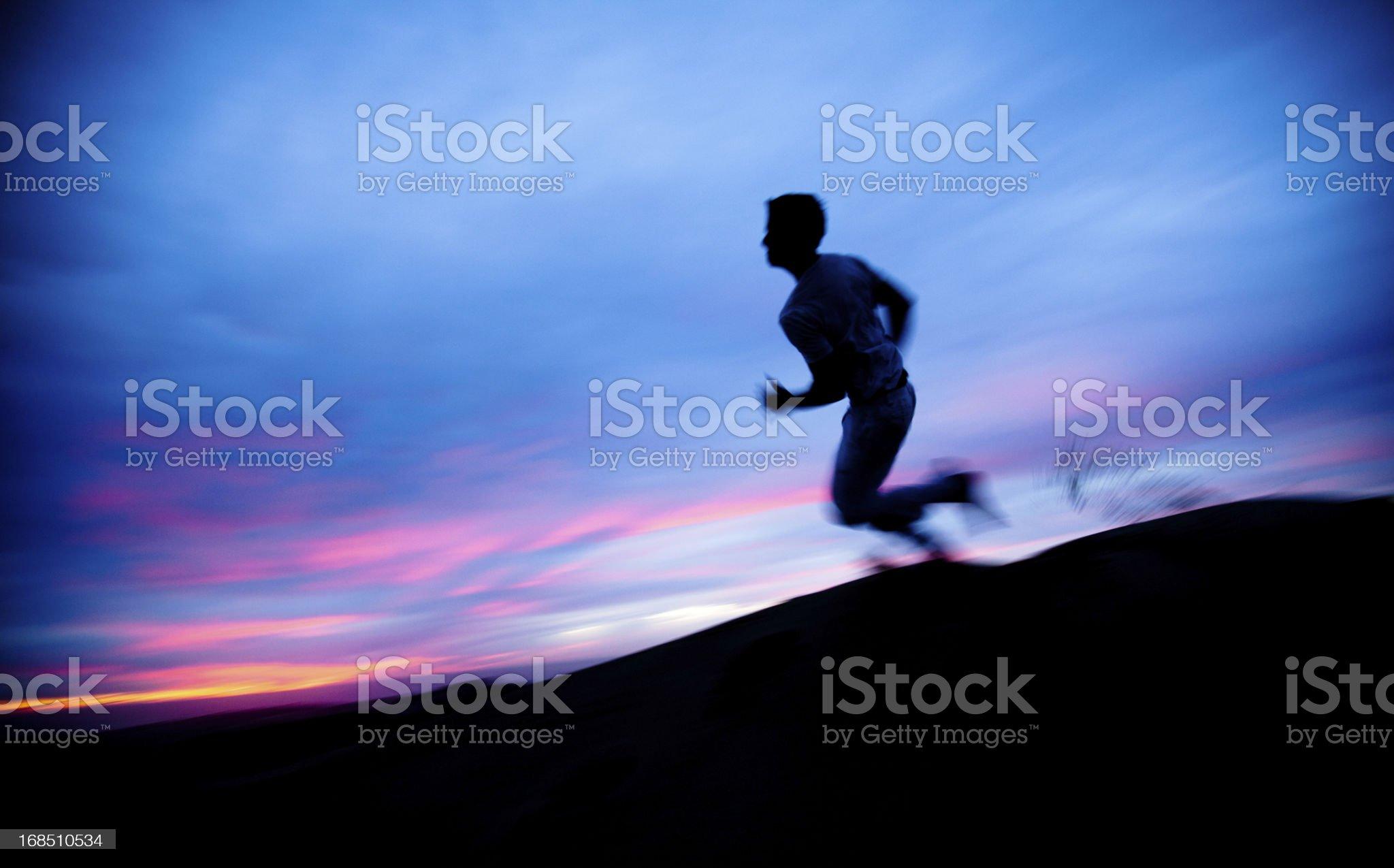 Solitary figure running through the desert at sunset royalty-free stock photo