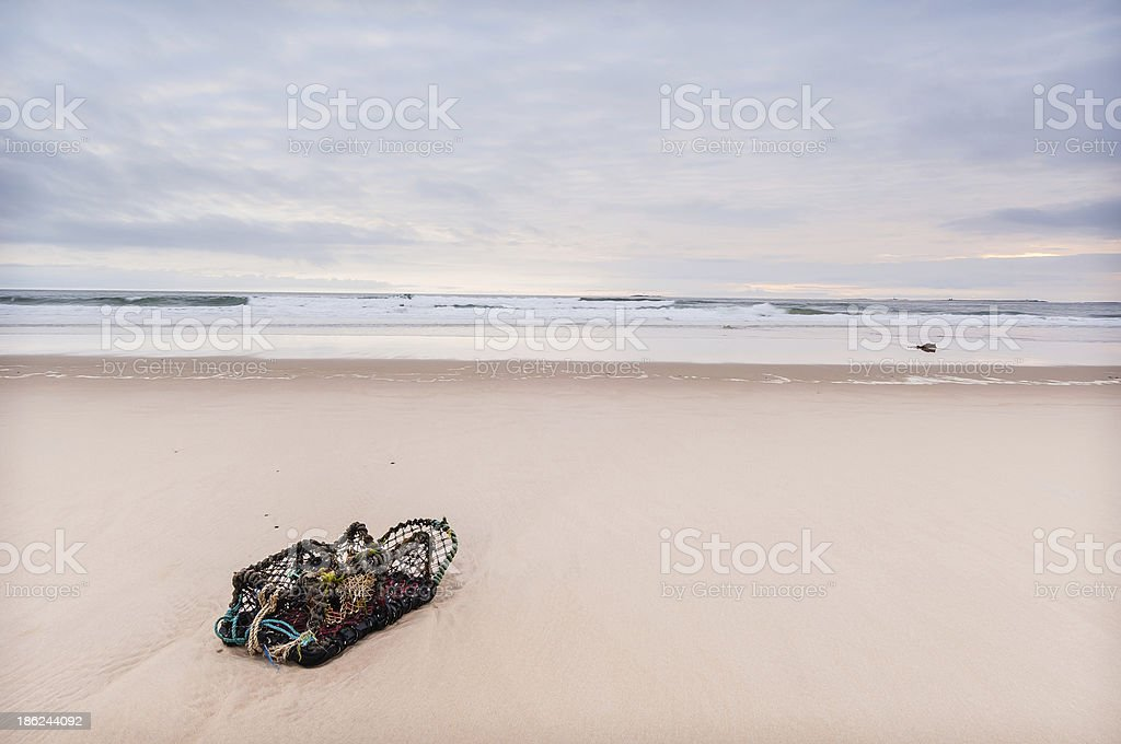 Solitary lobster pot lonely pale beach Bamburgh Northumberland stock photo