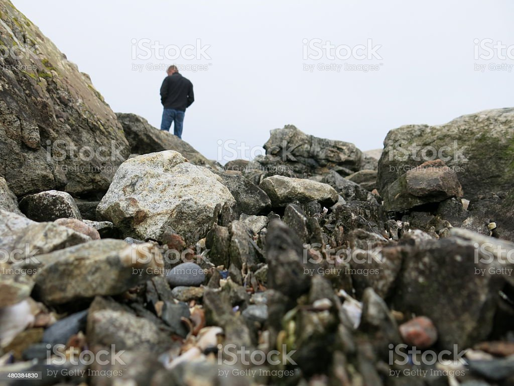 Solitary Man on Rocks of Acadia National Park Shore, Maine stock photo