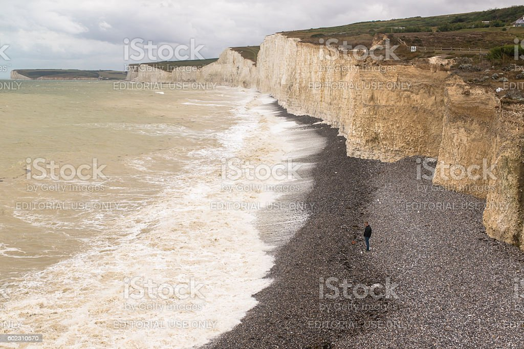 Solitary man standing alone on a gravel beach stock photo