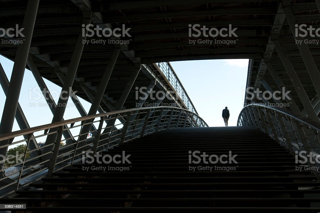 Solitary man walking through a tunnel into the light. stock photo