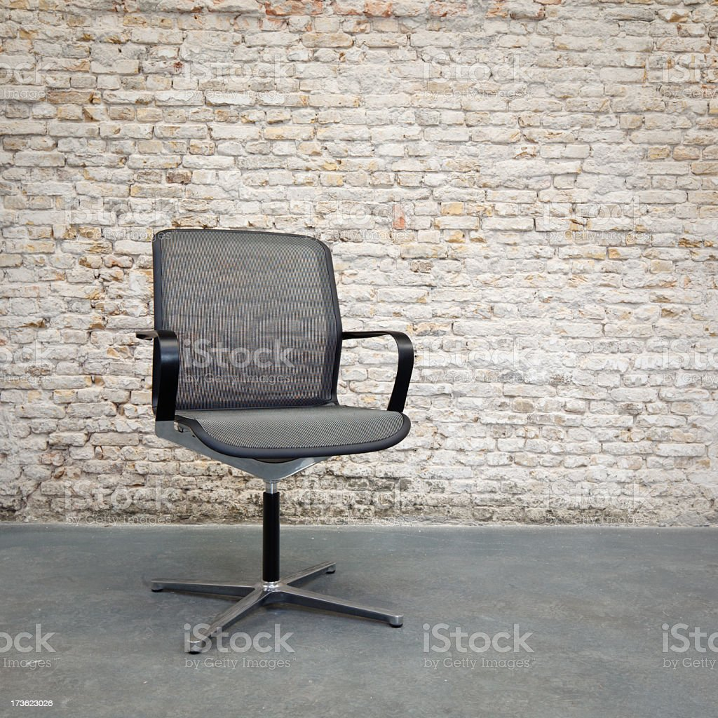 Solitary office chair in front of brick wall royalty-free stock photo