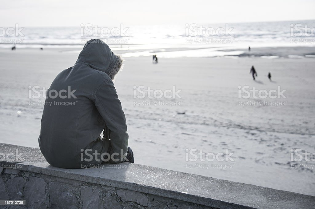 Solitary person in hooded parka coat sits on sea wall alone stock photo