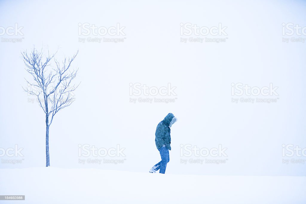 Solitary person walking alone in the snow stock photo