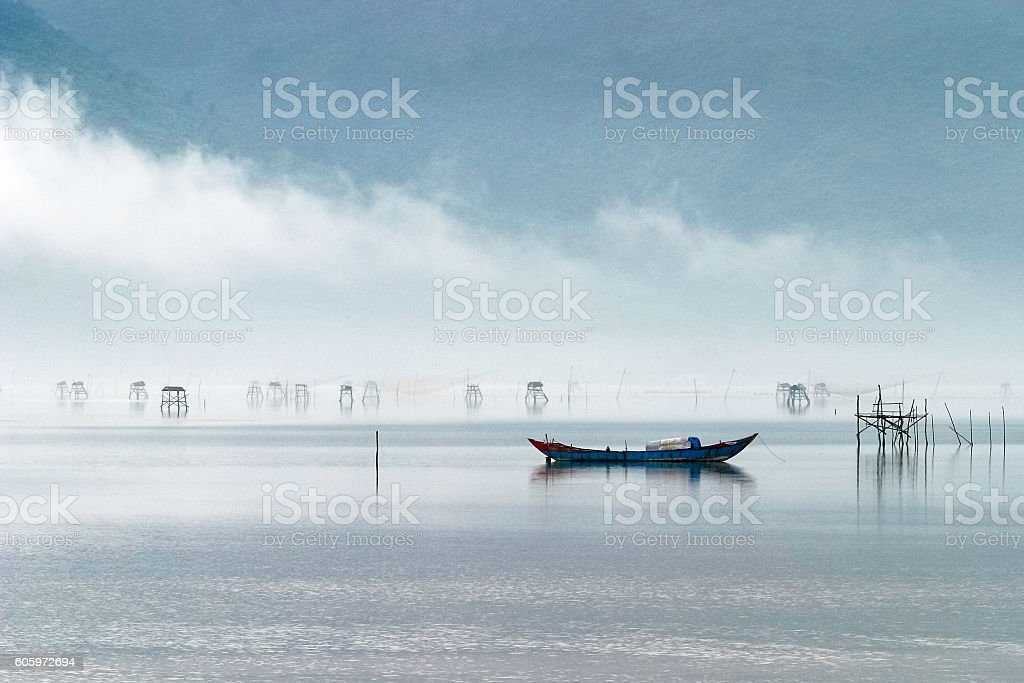 Solitary small traditional fishing boat in misty Vietnam lagoon stock photo