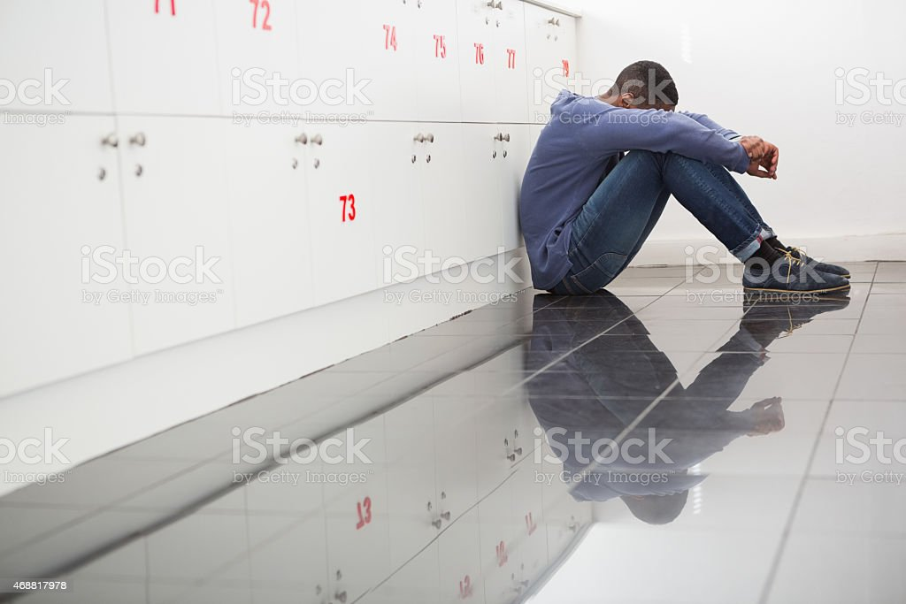 Solitary university student sitting on the floor stock photo