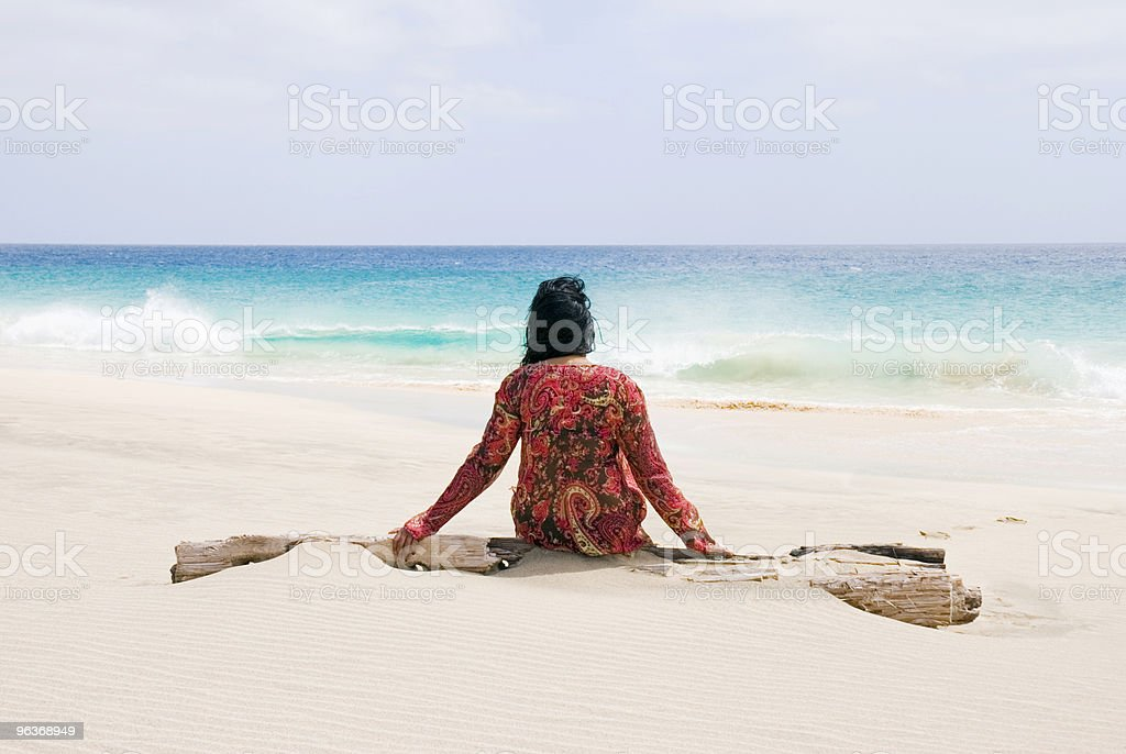Solitary woman in red on the beach, waiting for high tide stock photo