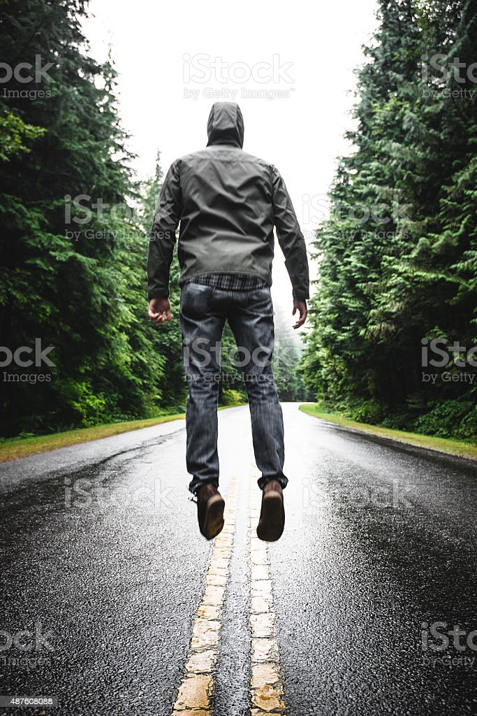 Solitude man jumping on the road stock photo