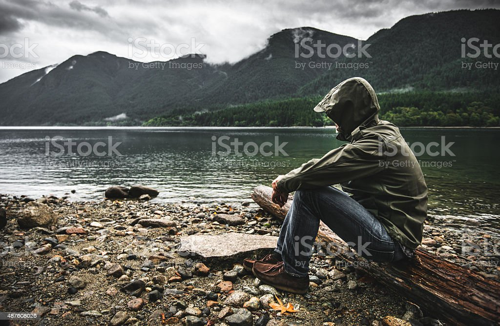 Solitude man pensive on the lake side stock photo