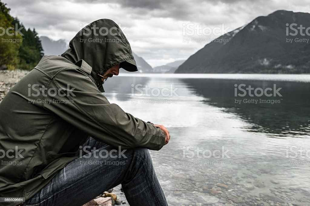 Solitude man pensive on the lake side stock photo