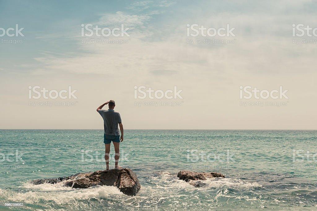 Solitude, Man stood on a rock at Pedn Vounder Beach stock photo