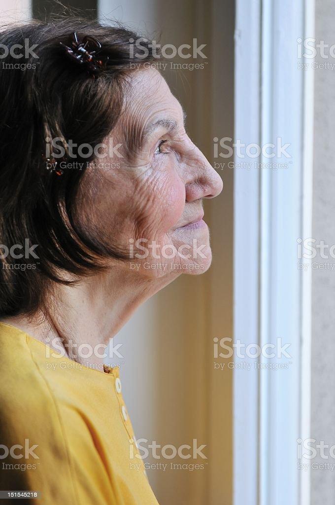 Solitude - senior woman looking through window royalty-free stock photo