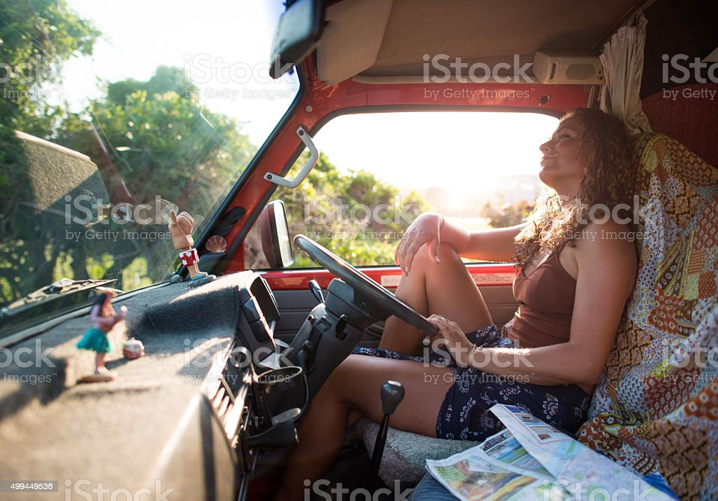 Solo female traveller sitting in van at sunset in Byron stock photo