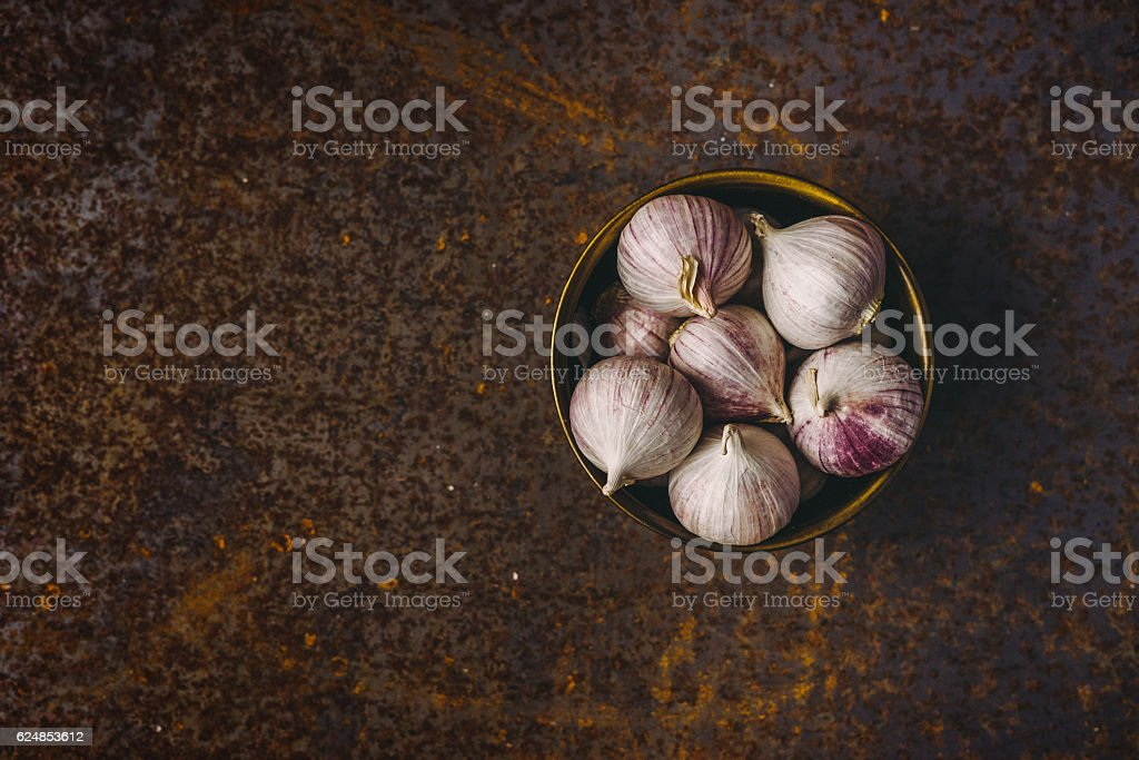 Solo garlic in a metal bowl on rusty background stock photo