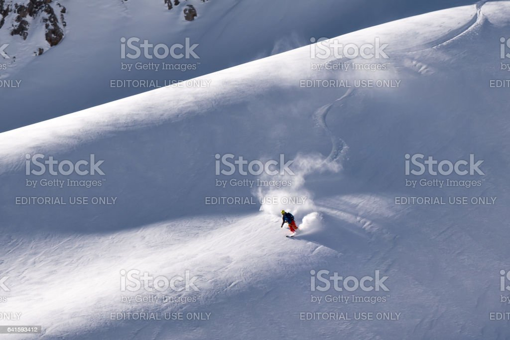 Solo lone skier putting down fresh first tracks on mountain ridge in winter stock photo