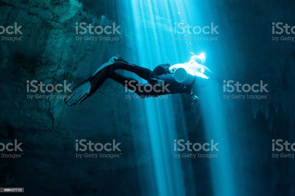 solo tech diver going through laser beams of light in the pit 7 stock photo
