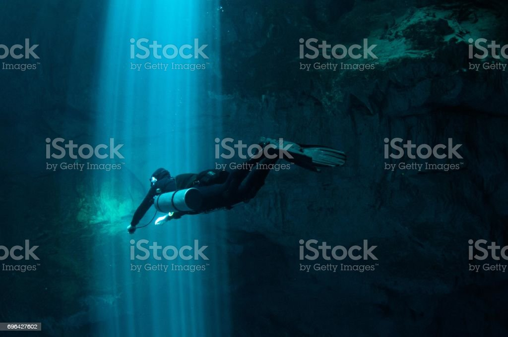 solo tech diver going through laser beams of light in the pit series 3 stock photo