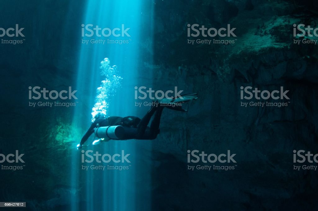 solo tech diver going through laser beams of light in the pit series 4 stock photo