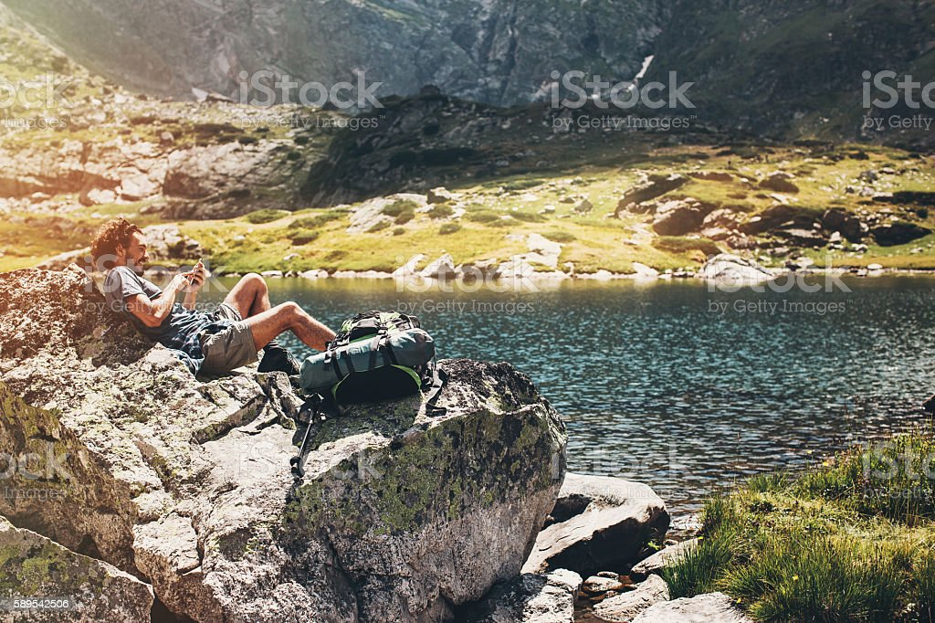 Solo traveler lying on a rock and texting stock photo
