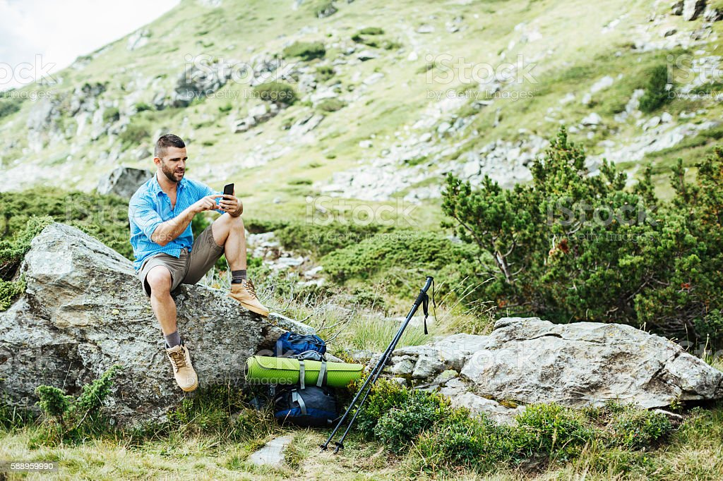 Solo traveler texting on a rock stock photo