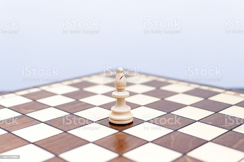 Solo white bishop chess piece on chess board stock photo