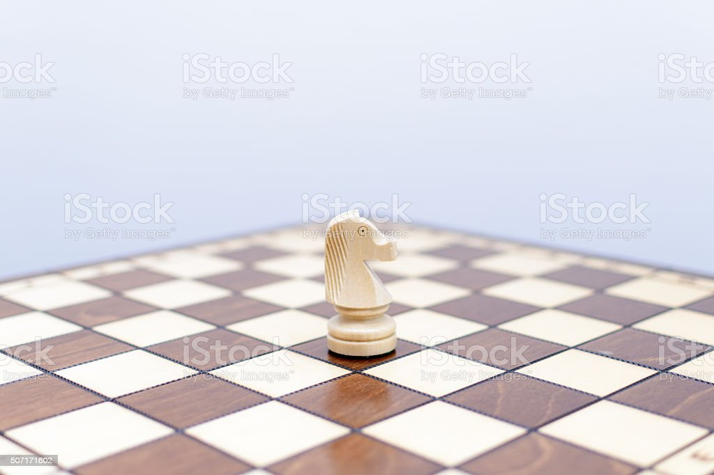 Solo white knight chess piece on chess board stock photo