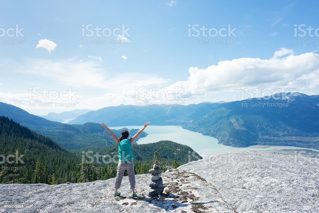 Solo Woman Hiker Celebrating at Summit Next to Rock Cairn stock photo