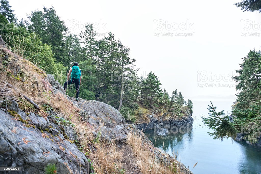 Solo Woman Hiker with Backpack Enjoying Ocean View from Mountain stock photo