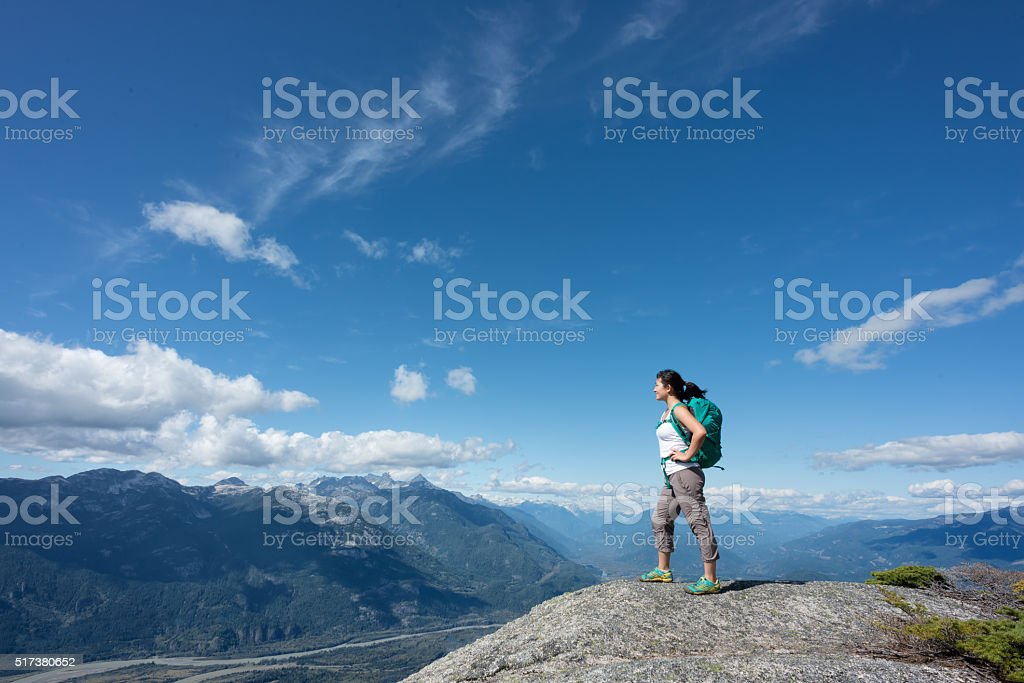 Solo Woman Hiker with Backpack Enjoying View from Mountain Summit stock photo