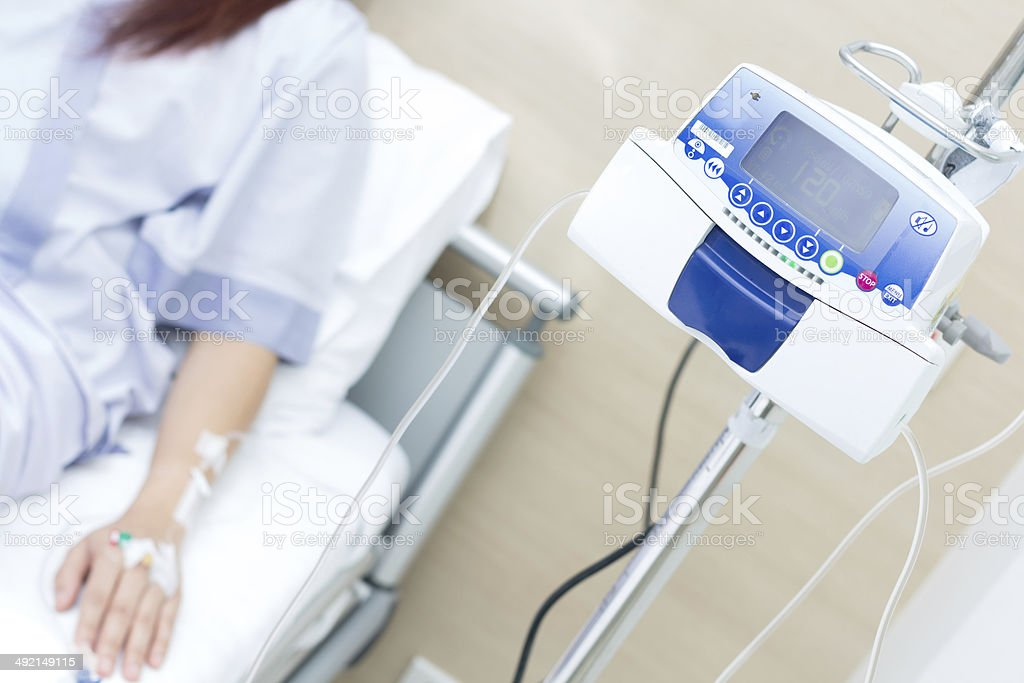 IV solution in a patient hand and IVS machine stock photo