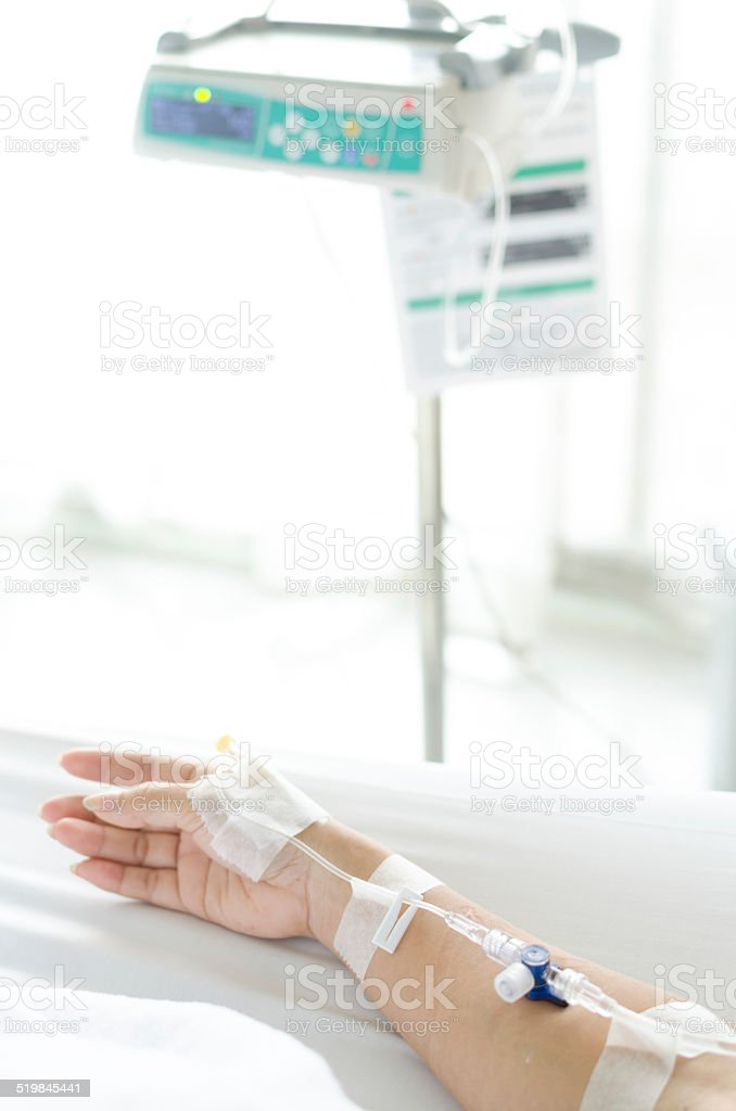 IV solution in a patient hand with IV machine stock photo