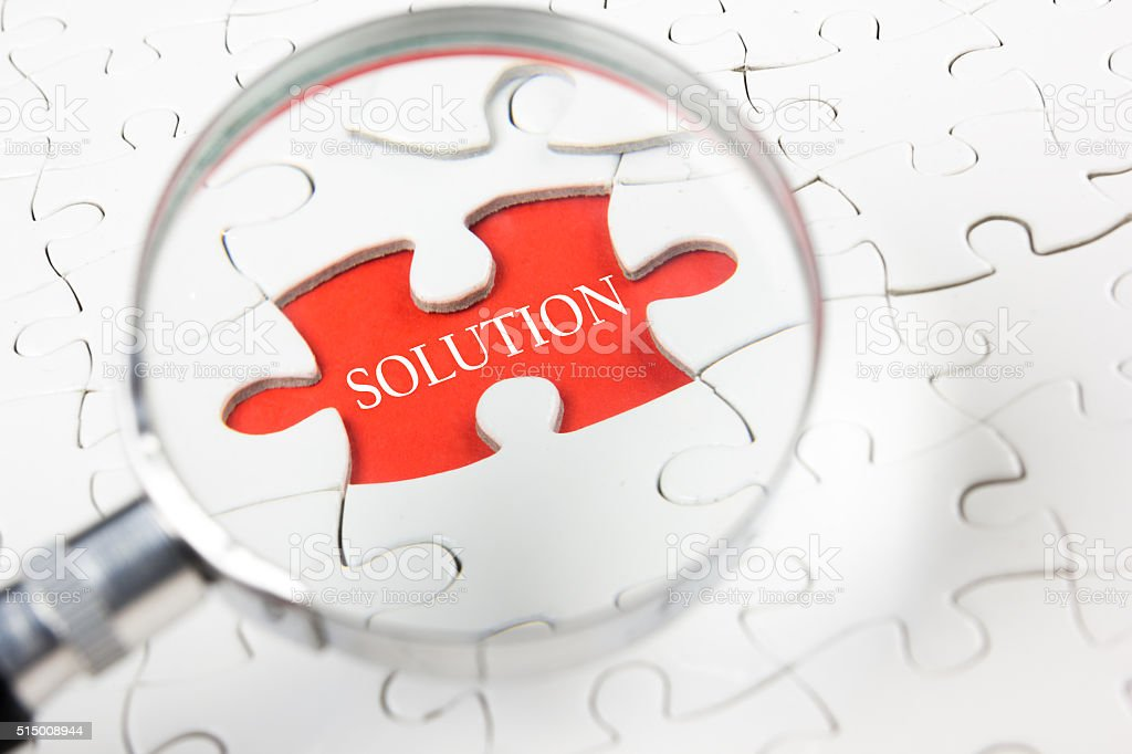 Solution word with hand holding magnifying glass over jigsaw puzzle stock photo