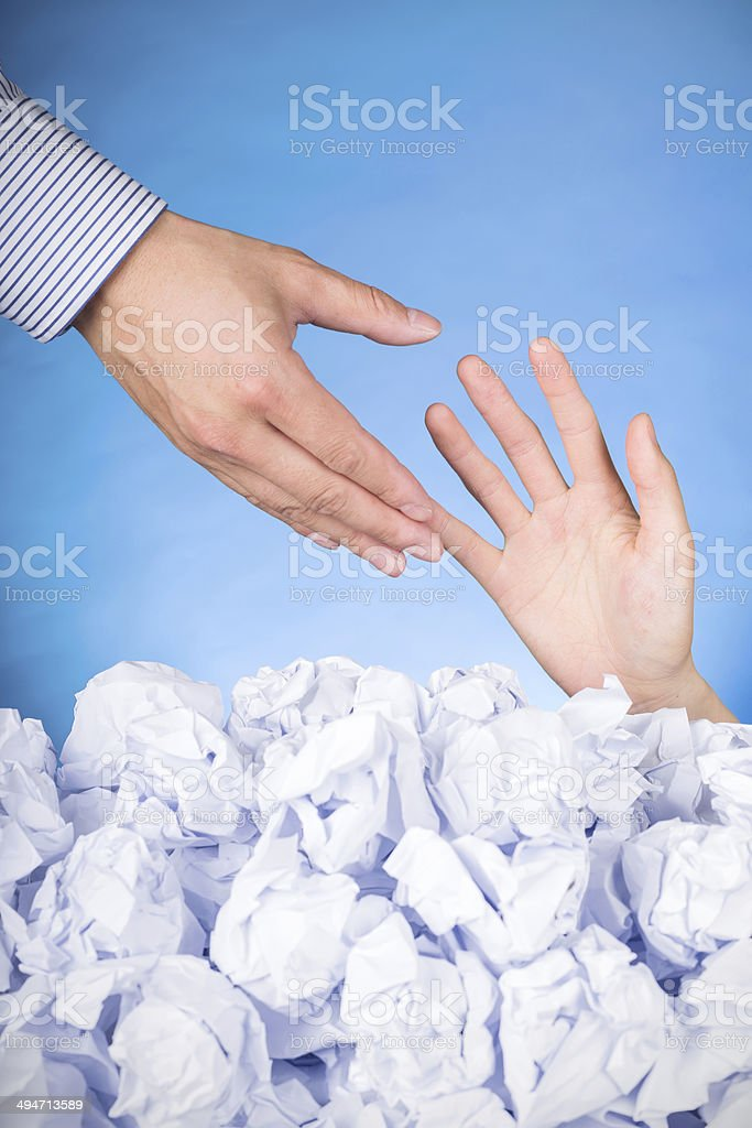solutions for bussiness problems:hand in crumpled pile of papers stock photo