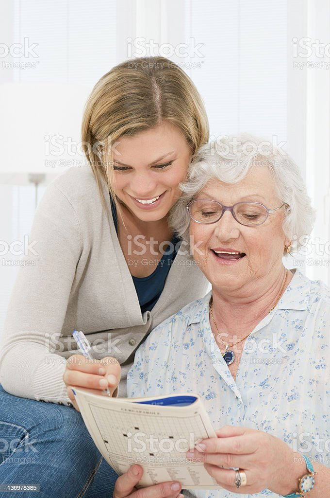 Solving crosswords puzzle together stock photo
