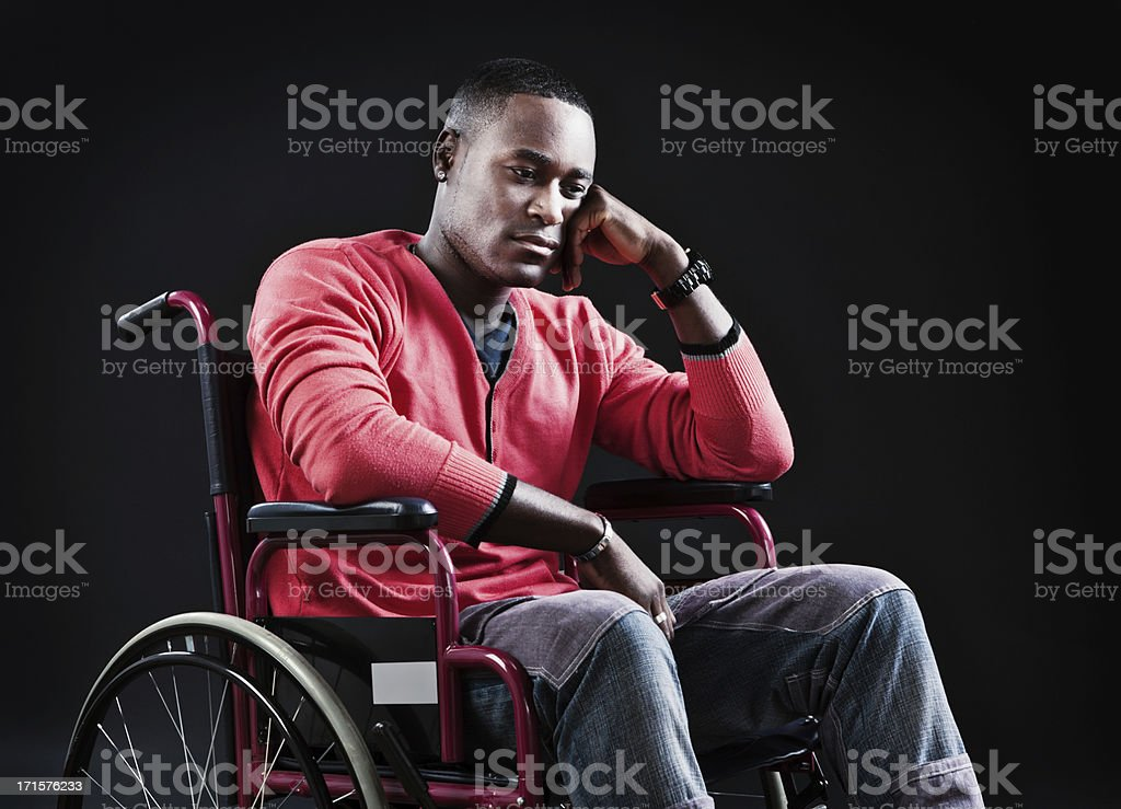 Somber young man sitting in wheelchair looks depressed royalty-free stock photo