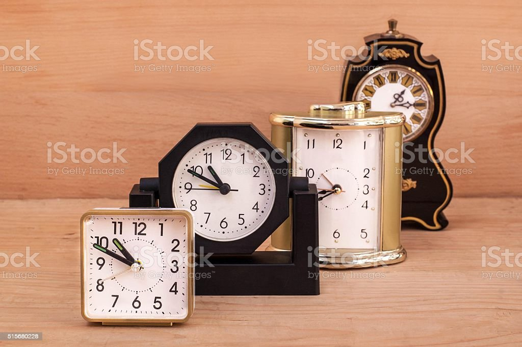 Some alarm clocks on a wooden background stock photo