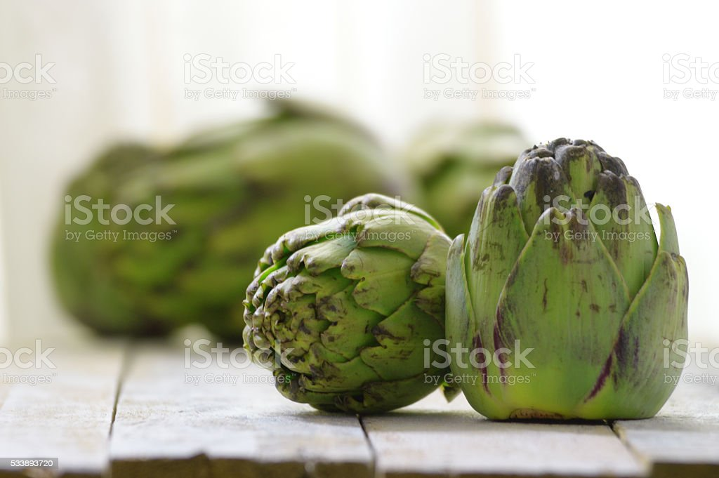 Some artichokes on a white wooden table stock photo