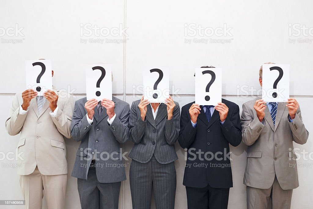 Some businessmen cover their faces with a question mark sign royalty-free stock photo