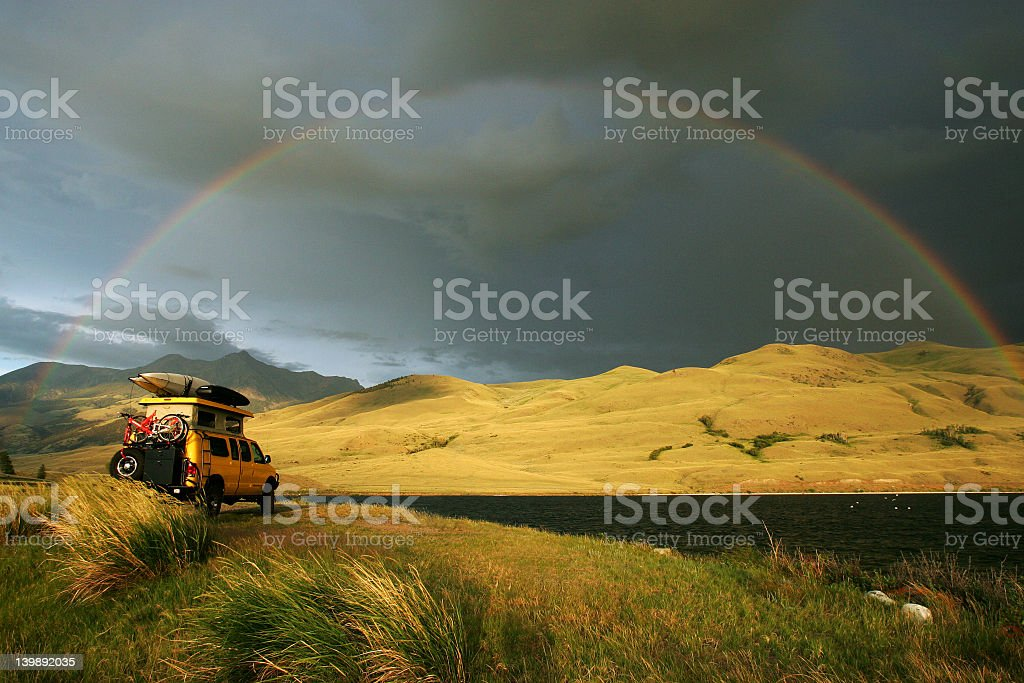 Some camping in a yellow truck with belongings on top stock photo
