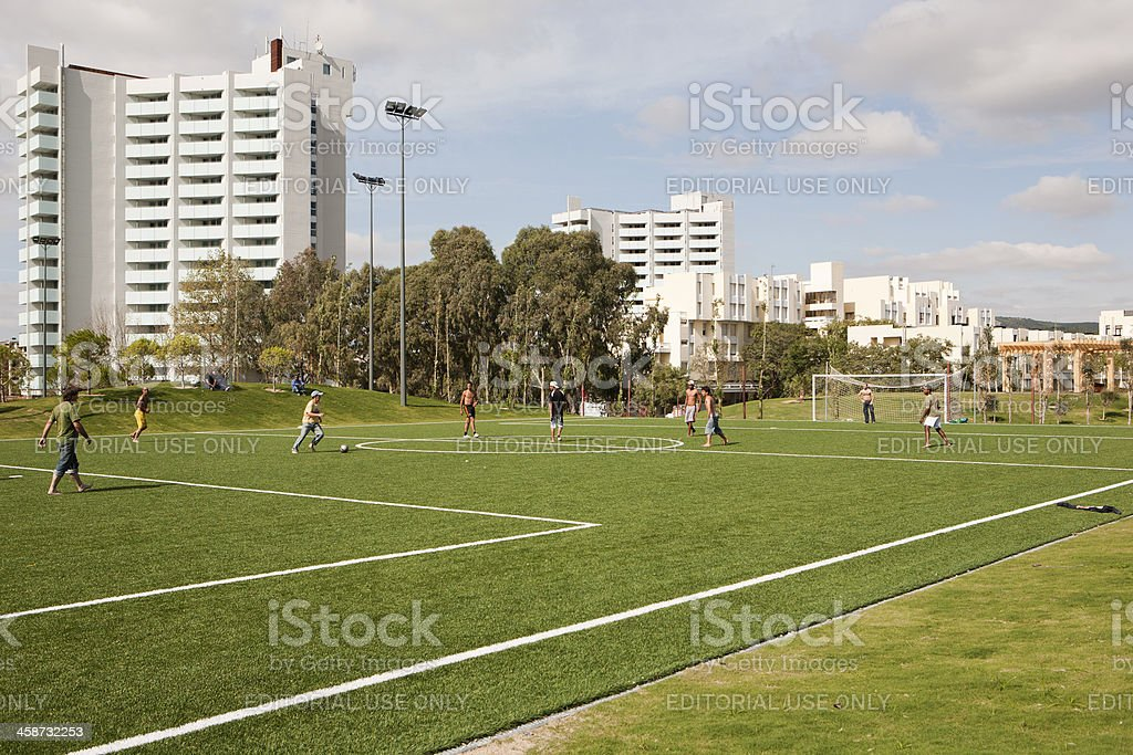 some guys playing soccer during a sunny day stock photo