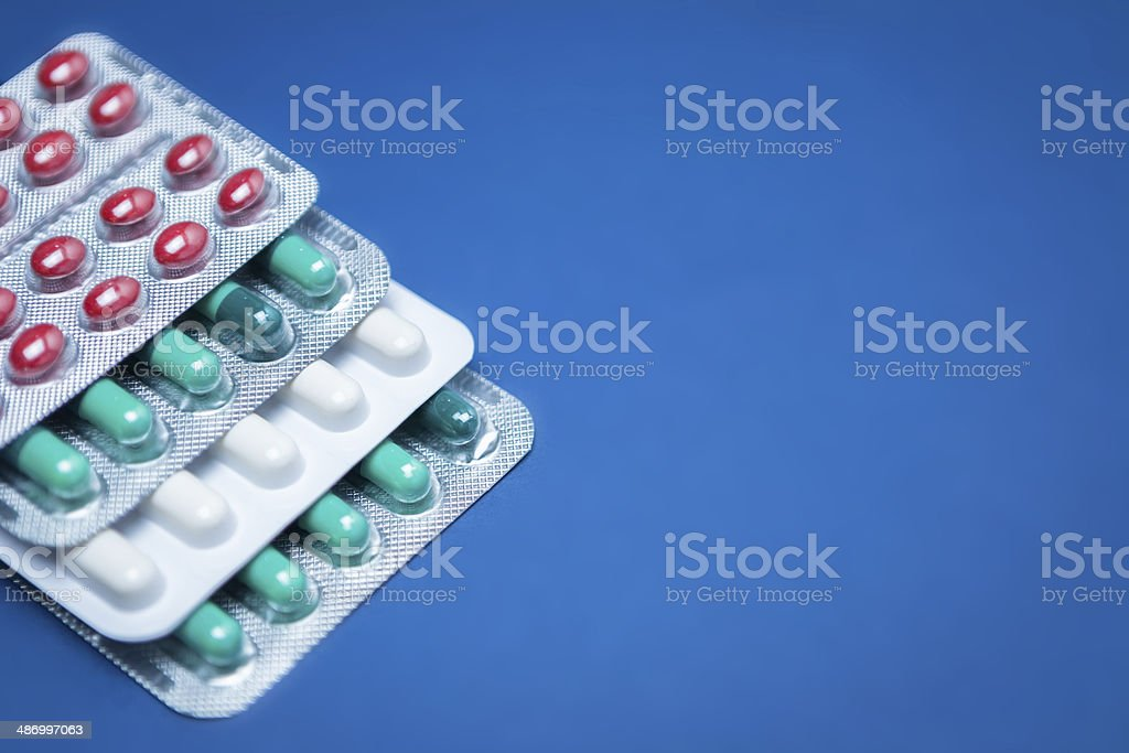 Some pills aligned isolated on blue background stock photo