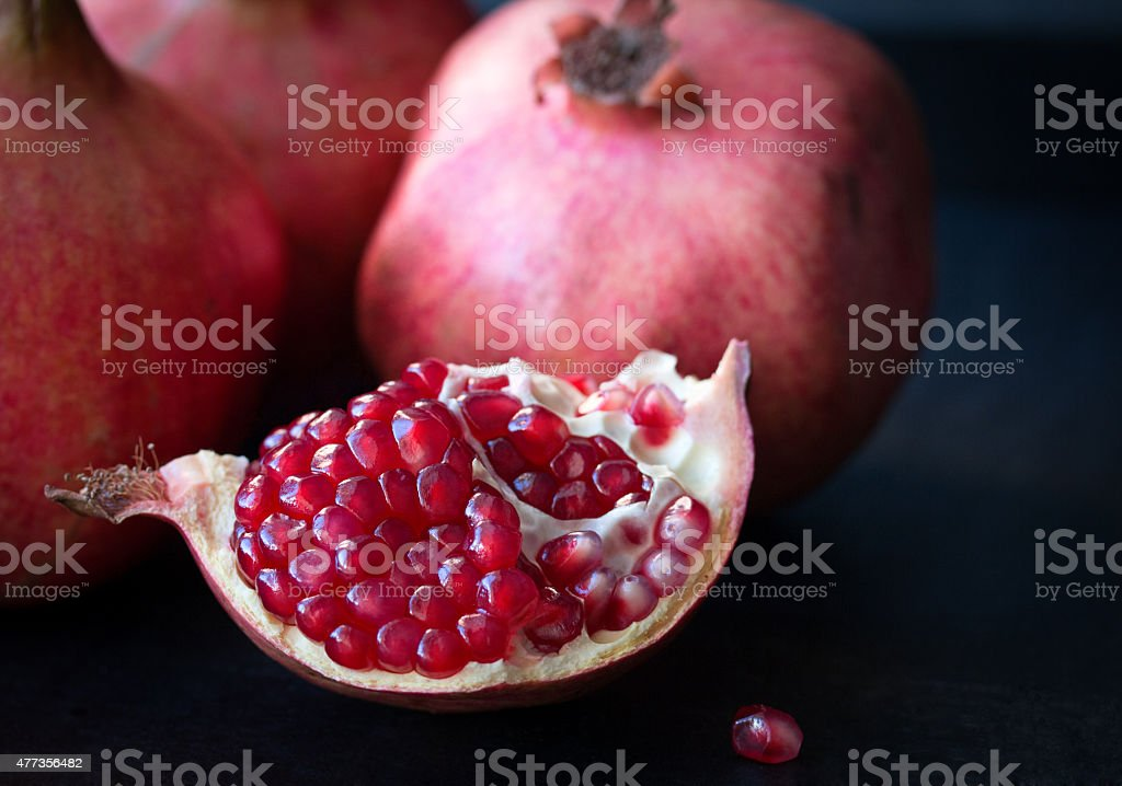 Some red pomegranates on black slate plate stock photo