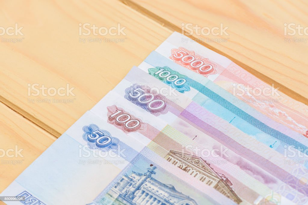 Some Russian money, bank note rubbles on wooden background stock photo