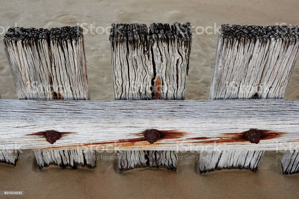 Some rustic textured wood barriers dividers on a sandy beach, rust and old nails stock photo