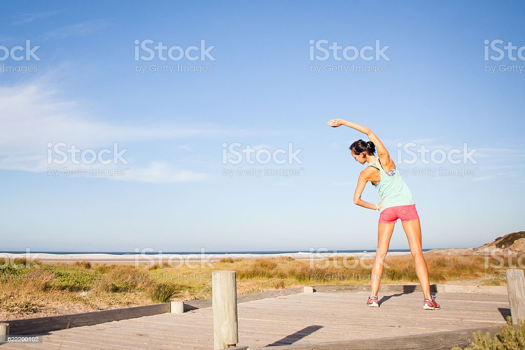Some yoga stretches on the boardwalk by the beach stock photo
