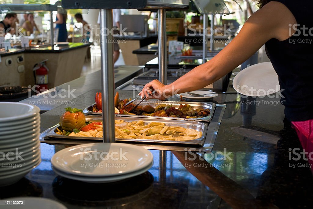 Somebody taking a spoonful from a tray of food at a buffet royalty-free stock photo
