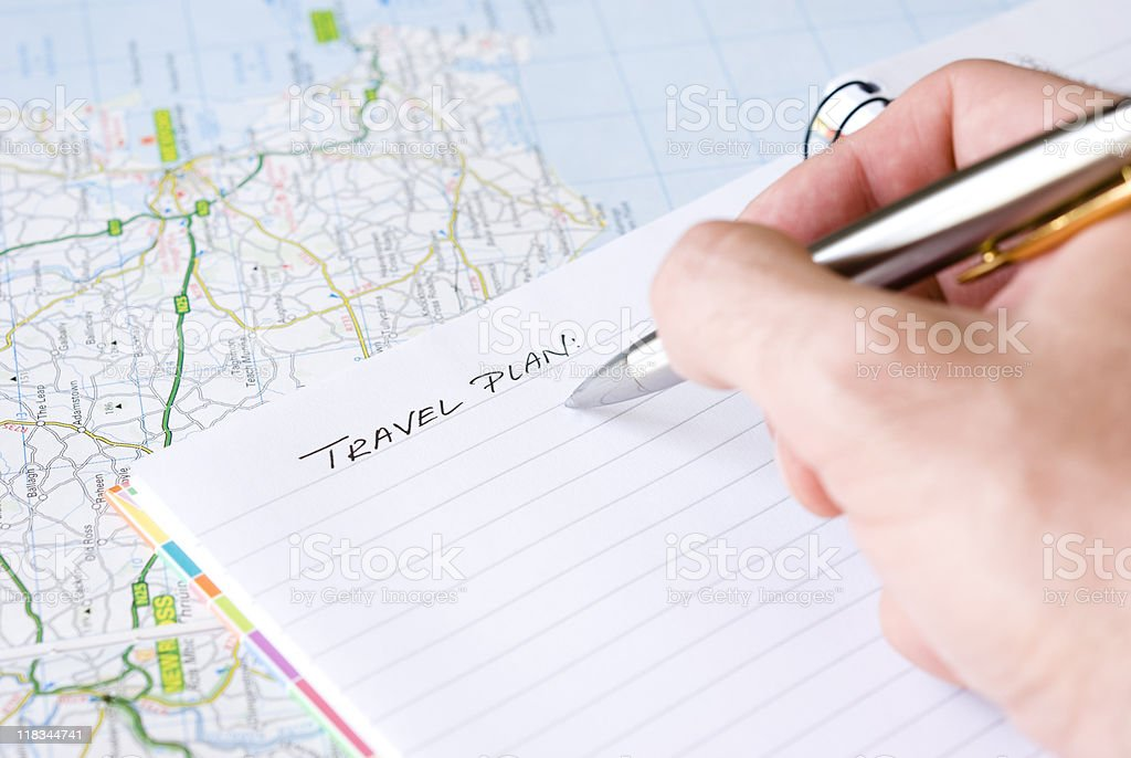Someone beginning to write travel plans in a pad on a map royalty-free stock photo